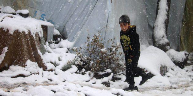 Un niño camina bajo la nieve en un campo de refugiados cerca de Burayqah, el pasado 26 de