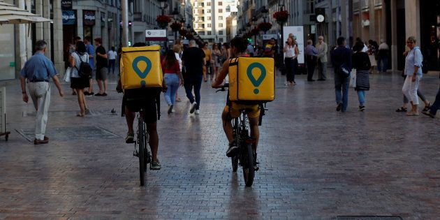 Delivery drivers for Glovo cycle in downtown Malaga, Spain, June 7, 2018. REUTERS/Jon