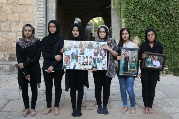 Ashwaq Haji posa con otras jóvenes yazidíes, sosteniendo retratos de víctimas del ISIS en su