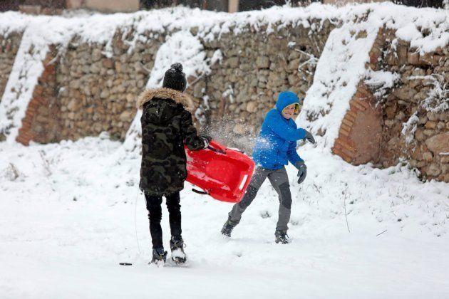 Dos chicos juegan en la nieve hoy en Montbui