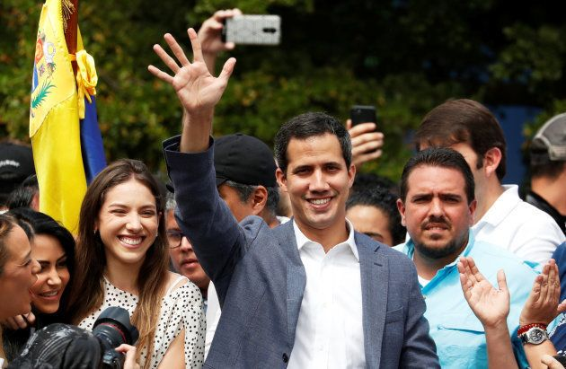Venezuela's opposition leader Juan Guaido waves to his supporters during a rally with members of the...