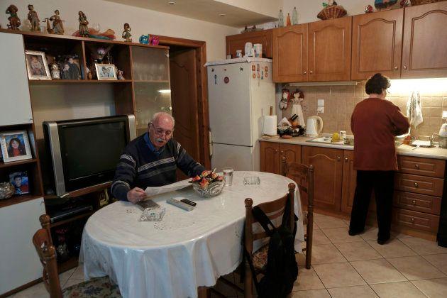 Yorgos Vagelakos lee el periódico mientras su esposa Anna lava los platos, en su casa del distrito de...
