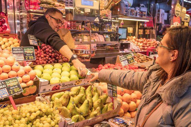 Una señora compra en una frutería del Mercado de Antón Martín, en