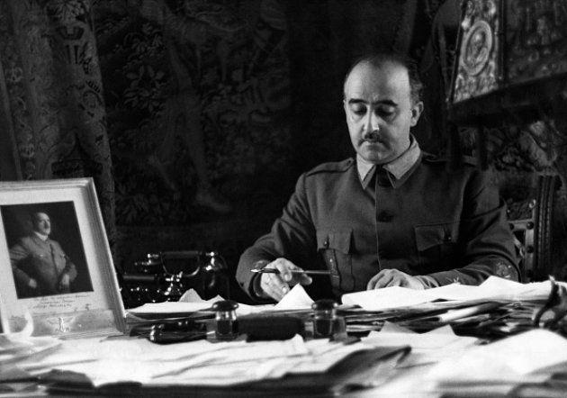Francisco Franco, en su despacho, con una foto de Adolf Hitler sobre el