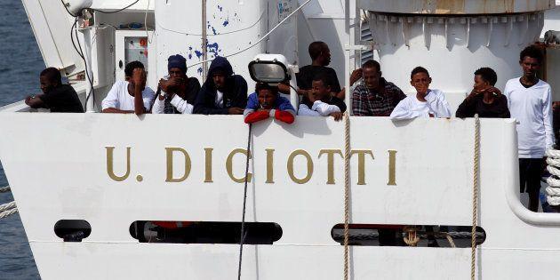 Un grupo de los inmigrantes que siguen en el 'Diciotti', asomados al muelle del puerto de Catania en...