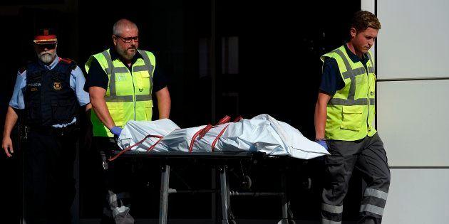 El cuerpo del atacante de Cornellá, transportado por personal especializado a la salida de la