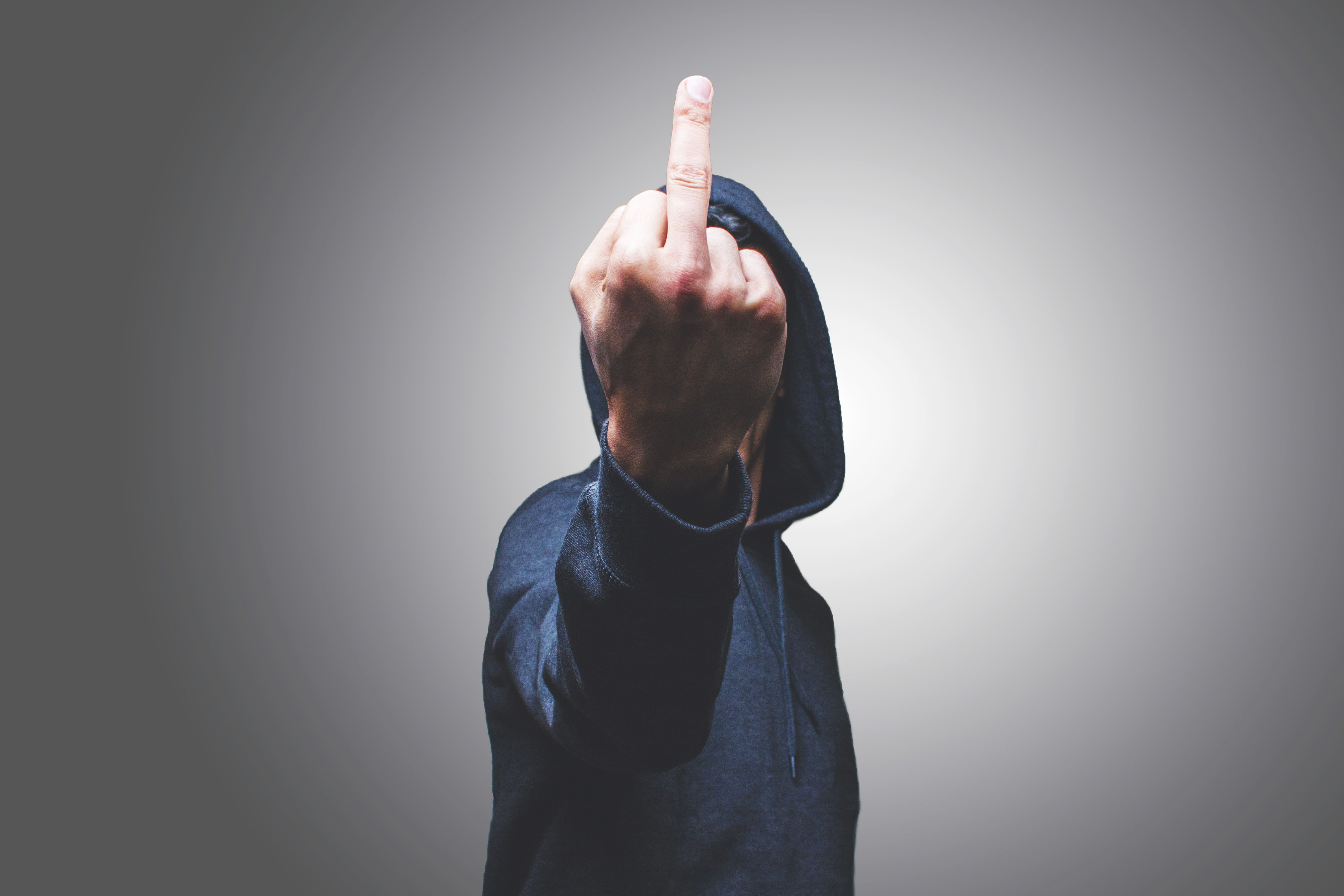 view of a man showing his middle finger hiding his face