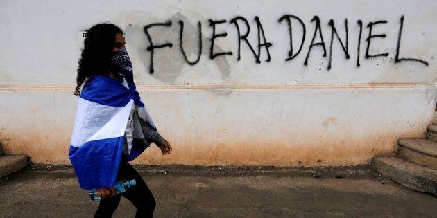 Una joven manifestante pasa ante una pintada contra Daniel Ortega, el pasado 25 de agosto en Granada,