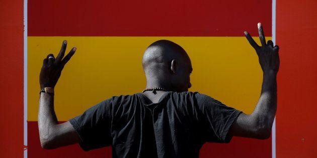 Un joven subsahariano hace un gesto de victoria ante una bandera de España, tras llegar al puerto de...