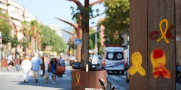 Unos vecinos del barrio pasan ante unos lazos amarillos en el barrio de Sants de