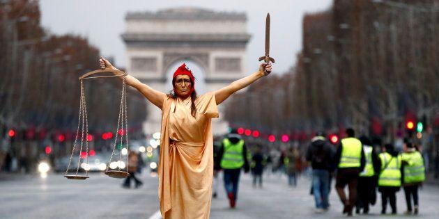 Una manifestante disfrazada como 'Marianne' posa durante una protesta de los chalecos amarillos en París,...