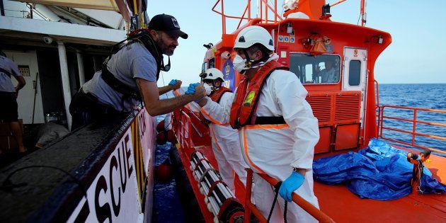 Un tripulante del 'Open Arms' y un funcionario de Salvamento se saludan el pasado 8 de agosto, cuando...