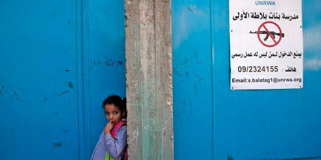Una niña espera en la entrada de una escuela gestionada por la UNRWA en