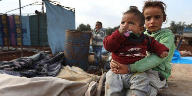 Niños sirios recién llegados con su familia a su 'nuevo hogar', una improvisada tienda en el campo de...