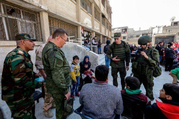 Soldados rusos y sirios con civiles evacuados de la zona de Guta (marzo,