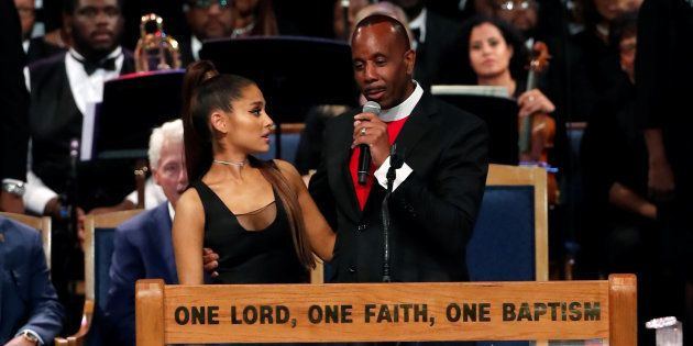 El pastor Charles Ellis habla mientras mantiene sujeta a Ariana Grande en el funeral de Aretha