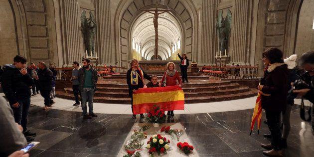 Un grupo de personas posa con una bandera de España en la tumba de Francisco Franco, el pasado
