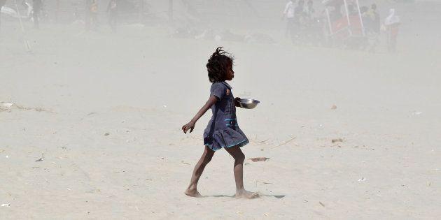 Una niña hindú camina en mitad de una tormenta de arena en las orillas en Ganges, en Allahabad, en febrero...