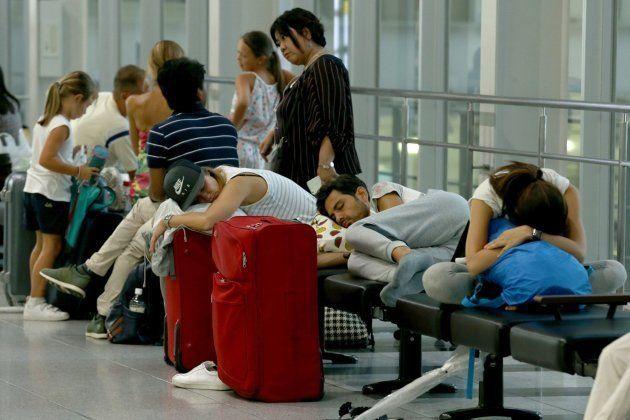 Turistas extranjeros duermen en los bancos de una estación de trenes de