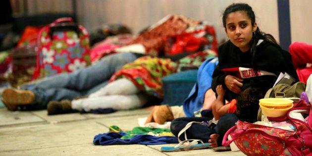 Una joven venezolana amamanta a su bebé mientras espera el trámite en el paso fronterizo de Tumbes, Perú,...