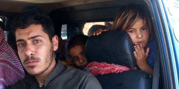 Una familia siria, en su coche, yendo a zonas más seguras del norte de la provincia de Idlib, ante la...