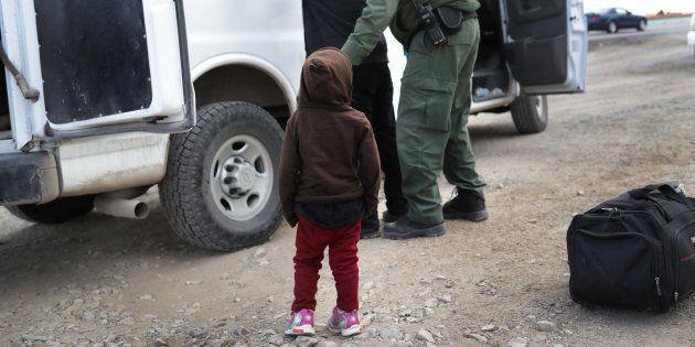 Un niño observa cómo un policía de fronteras de EEUU cachea a un inmigrante adulto, el pasado 1 de febrero...