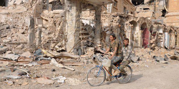 Unos hombres pasan en bicicleta ante las ruinas de un edificio en Deir Ezzor, el pasado
