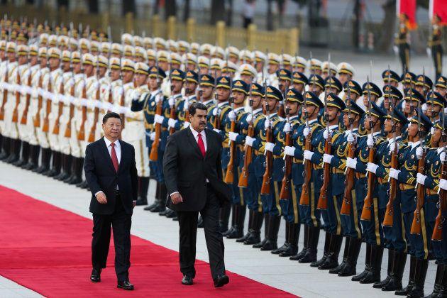 Xi camina junto a su homologo venezolano, Nicolás Maduro, en su reciente visita a