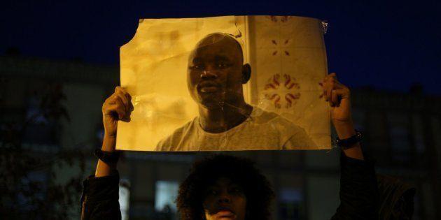 Una joven alza la foto de Mame Mbaye durante una concentración antirracista en