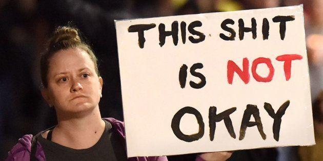 Una manifestante alza un cartel de protesta contra el racismo en Oakland en el que se