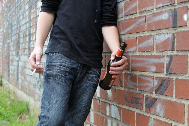 Un joven bebe cerveza y fuma, en una imagen de