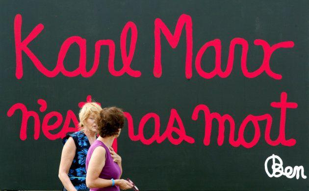 Unas mujeres pasan ante un cartel que dice: