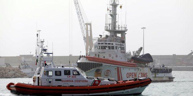 Un grupo de migrantes espera para desembarcar de la nave de Proactiva Open Arms en el puerto siciliano...