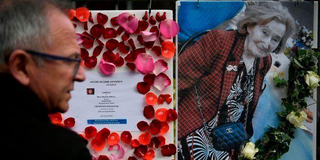 Un hombre pasa ante la foto de Mireille Knoll y los mensajes que convocan a una marcha en su memoria,...