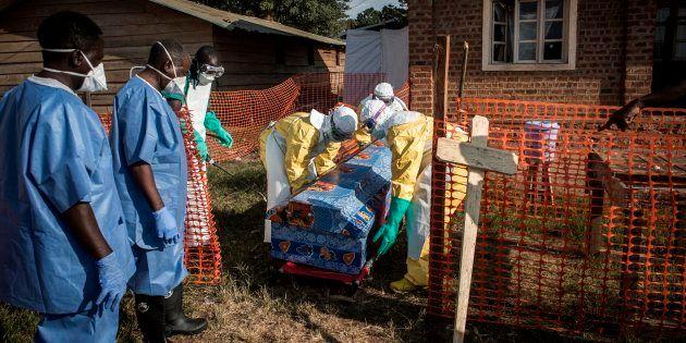 Personal médico desinfecta el féretro de un hombre muerto, en un caso no confirmado de ébola, en un centro...