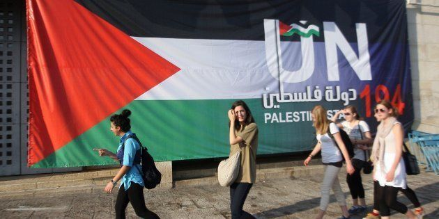 Un grupo de turistas pasa ante una pancarta en Belén (Cisjordania), en la que se reclama que Palestina...