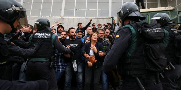 Un grupo de manifestantes, controlado por la Guardia Civil ante un colegio electoral de Sant Julia de...