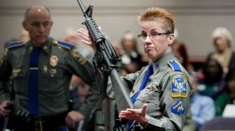 FILE - In this Jan. 28, 2013, file photo, firearms training unit Detective Barbara J. Mattson, of the Connecticut State Police, holds up a Bushmaster AR-15 rifle, the same make and model of gun used by Adam Lanza in the Sandy Hook School shooting, for a demonstration during a hearing of a legislative subcommittee reviewing gun laws, at the Legislative Office Building in Hartford, Conn. Lawyers for a survivor and relatives of nine killed in the shooting filed papers Tuesday, Nov. 15, 2016, asking the state Supreme Court to hear their appeal of a wrongful-death lawsuit dismissed in October 2016 against Remington Arms. (AP Photo/Jessica Hill, File)