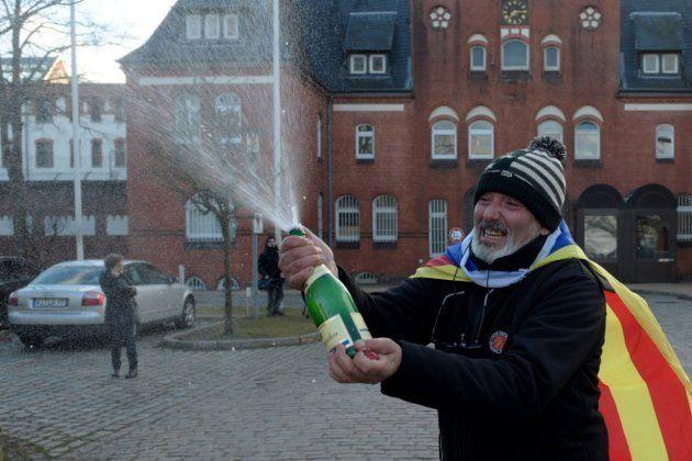 Un hombre con una bandera estelada celebra con champán frente la cárcel de Neumünster, donde permanece...