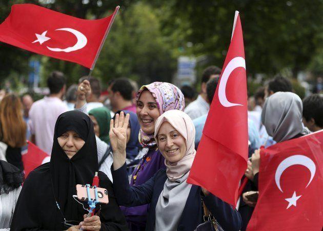 Mujeres turcas ondean banderas de su país en la víspera del primer aniversario del fallido golpe de Estado...