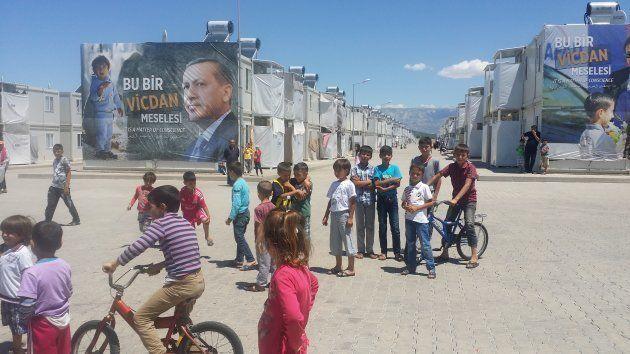 Niños refugiados miran y juegan. El cartel de atrás representa a un angustiado niño frente a Erdoğan,...