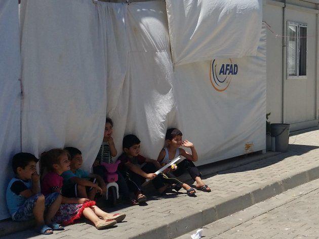 Varios niños ríen bajo la fina sombra proyectada por un contenedor vivienda. | Campo de
