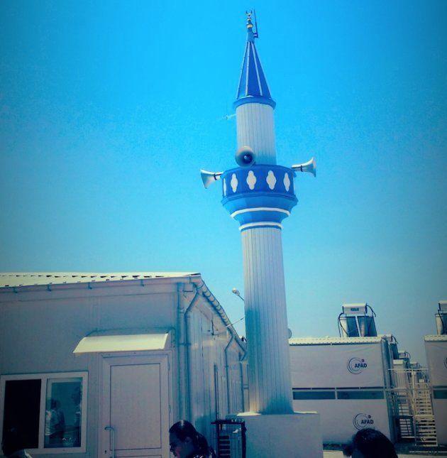 Un pequeño minarete se alza frente a la sencilla mezquita del campamento de