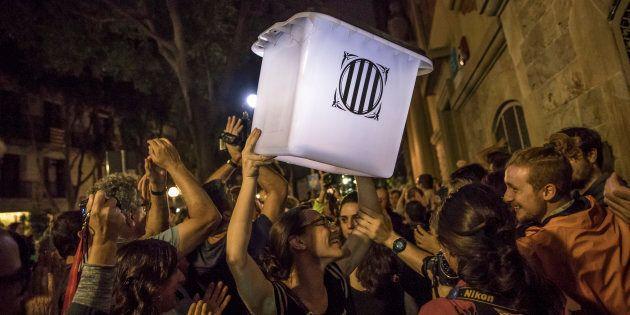 Un grupo de organizadores del referéndum del 1-O muestra una urna después de la