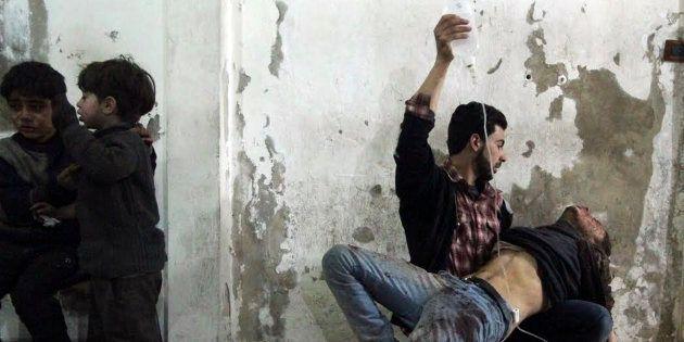 Un hombre ayuda con un gotero a otro, con un par de niños heridos cerca de ellos, en un hospital de campaña...