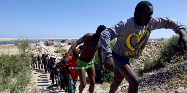 Un grupo de migrantes, retratados en la playa de Gharaboli, al este de Tripoli, tras ser rescatados el...