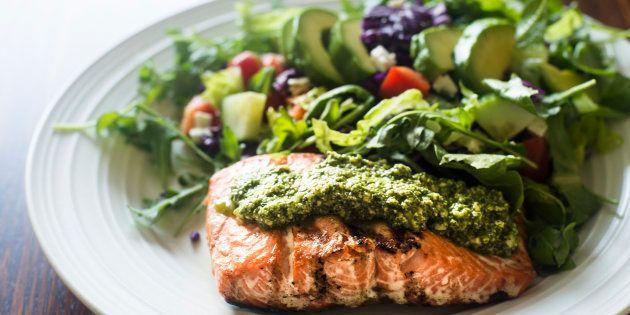Plato casero de salmón al pesto y ensalada de lechuga con aguacate, pepino, tomate, zanahoria y col