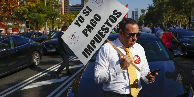 Un conductor de Cabify porta una pancarta que
