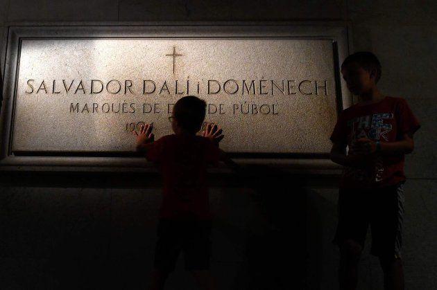 Un niño toca la inscripción sobre la tumba de Dalí, en el Teatro-Museo Dalí de Figueres