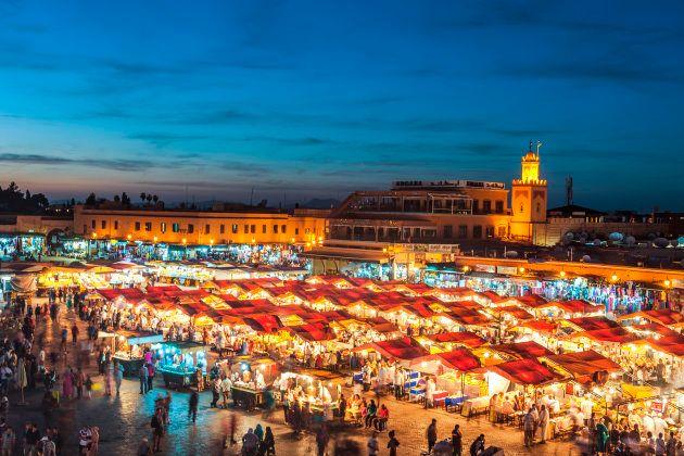 Atardecer en Marrakech, Marruecos, en la plaza Djemaa El Fna con la mezquita de